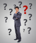 Businessman thinking surrounded by question marks — Stock Photo