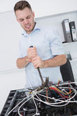 Frustrated man using hammer to pull out wires from cpu — Foto de Stock
