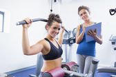 Smiling woman on weights machine with trainer — Stock Photo