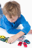 Close-up of boy playing with playhouse and toy cars — Stock Photo