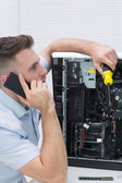 Young computer engineer working on cpu while on call — Stock Photo