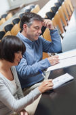 Man and woman taking notes during lecture — Stock Photo