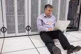 Mann sitzt im erdgeschoss mit laptop, die server zu überprüfen — Stockfoto