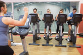 Enthusiastic woman teaching spinning class — Stock Photo