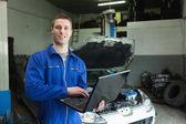 Auto mechanic working on laptop — Stock Photo