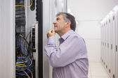 Man looking up thoughtfully into server locker — Stock Photo