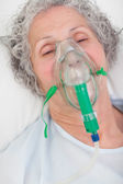 Elderly closing her eyes while lying in a hospital bed — Stock Photo