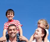 幸福的父母们给他们的孩子背驮式摆脱 — 图库照片