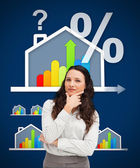 Thinking businesswoman standing against a energy efficient house — Stock Photo