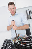 Portrait of frustrated man using hammer to pull out wires from c — Foto de Stock