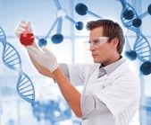 Scienctist examinando un líquido rojo — Foto de Stock