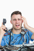 Portrait of frustrated computer engineer on call in front of ope — Stock Photo
