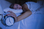 Awakening woman stopping her alarm clock — Stock Photo