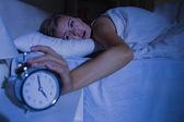 Awakening woman stopping her alarm clock — Stock Photo