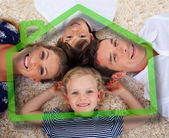 Smiling young family in front of green house illustration — Stock Photo