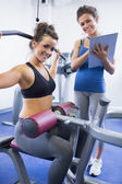 Happy female trainer and client on weights machine — Stock Photo