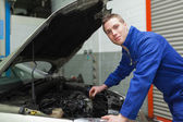 Confident mechanic checking car engine oil — Stock Photo