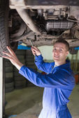 Mechanic in coveralls working under car — Stock Photo