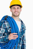 Portrait of smiling young male architect carrying coiled blue tu — Stock Photo