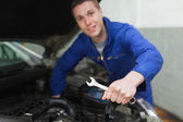 Auto mechanic with spanner repairing car — Stock Photo