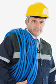 Mature man wearing hardhat with cable — Stock Photo