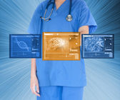 Doctor using touchscreen against blue background — Stok fotoğraf