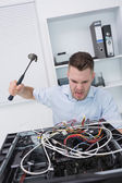 Frustrated man hitting cpu with hammer — Stock Photo