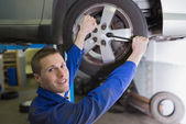 Male mechanic changing car tire — Stock Photo