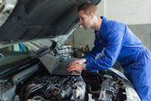 Auto mechanic working on laptop — Stock Photo