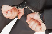 Businessman with handcuffs clencing fists — Stock Photo