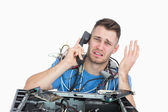 Frustrated computer engineer on call in front of open cpu — Stock Photo