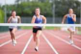 Athletes racing towards finish line — Stock Photo
