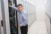 Man fixing wires of servers — Stockfoto