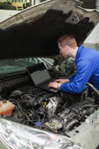 Mechanic using laptop on car engine — Stock Photo