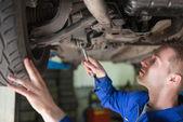 Auto mechanic working under car — Stock Photo
