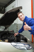Auto mechanic by car gesturing thumbs up — Stock Photo