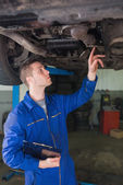 Auto mechanic with clipboard under car — Stock Photo