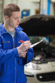 Auto mechanic writing on clipboard — Stock Photo