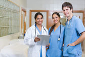 Smiling doctor and smiling male and female nurse in a hallway — Stock Photo