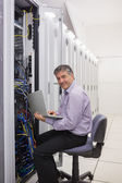 Man working on laptop to check servers — Stockfoto