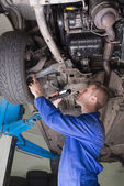 Auto mechanic examining under car — Stock Photo