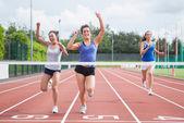 Athletes celebrating as they cross finish line — Stock Photo