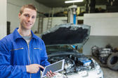 Happy mechanic using digital tablet — Stock Photo