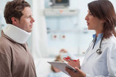 Doctor talking to a male patient with a collar on — Stock Photo