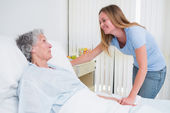 Smiling woman holding the hand of a patient in a room — Stock Photo