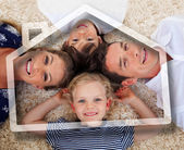 Smiling young family lying with heads together — Foto de Stock