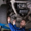 Happy mechanic under car — Stock Photo