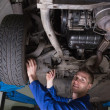 Happy mechanic under car - Stock Photo