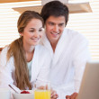 Couple using laptop over breakfast — Stock Photo #24100981