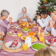 Family saying grace before christmas dinner — Stock Photo